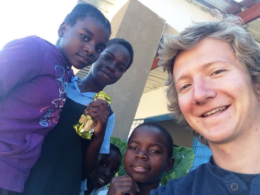 English student Jackson White with sixth graders from Libuyu Community School.