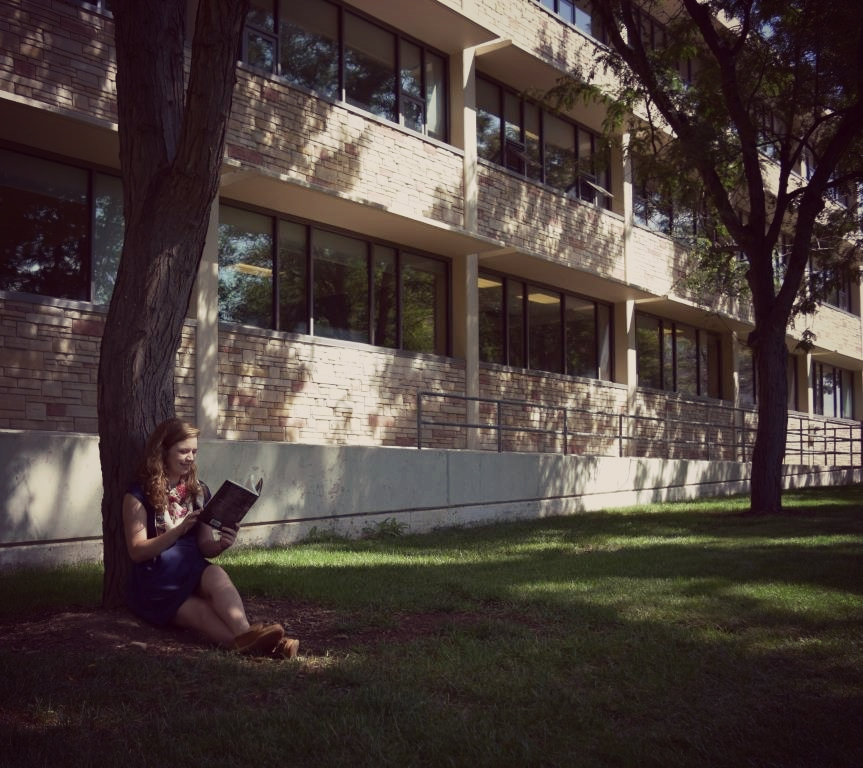 Communications intern Ashley Alfirevic relaxing with a book under the trees on the south side of Eddy Hall, a popular site for such things
