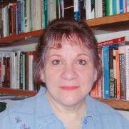 A photo of Marnie Leonard looking at the camera with a bookshelf in the background