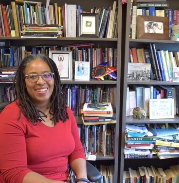 Camille Dungy sitting in front of a bookcase, looking at the camera and smiling