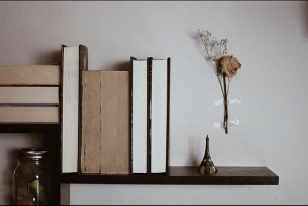 A shelf of books hanging on the wall with dried flowers.