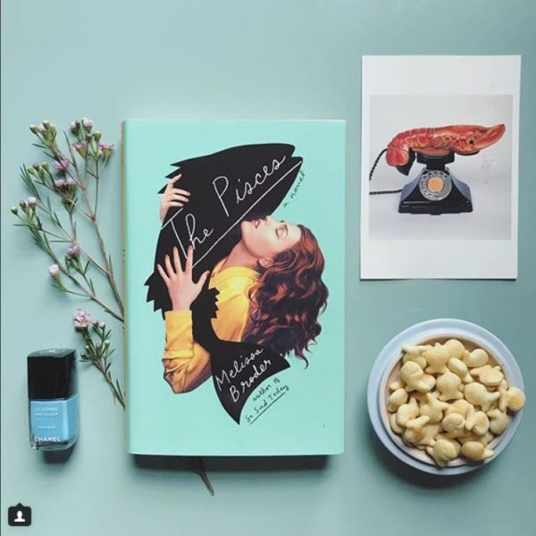 "A book called ""The Pisces"" surrounded by goldfish, nail polish, dried flowers, and Polaroids."