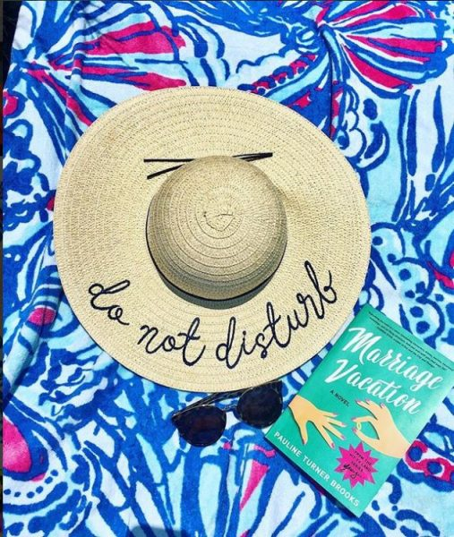 "A hat that says ""do not disturb"" laid on a beach towel with a book called ""Marriage Vacation."""