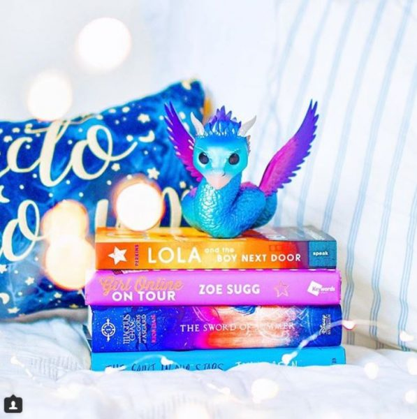 Stack of  bright books with a dragon on top