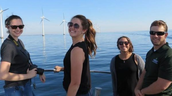 Group of students by the water with wind turbines in the background