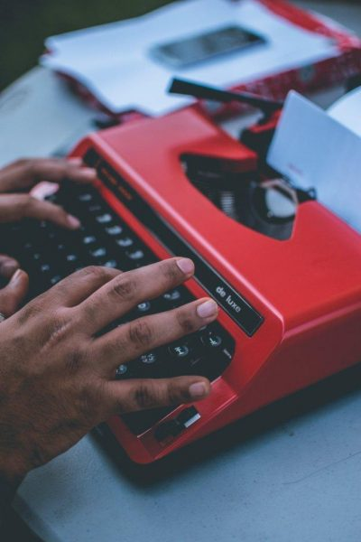 Hands typing on red typewriter