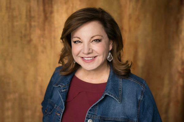 Donna Cooner in a jean jacket over a red shirt in front of a wood background